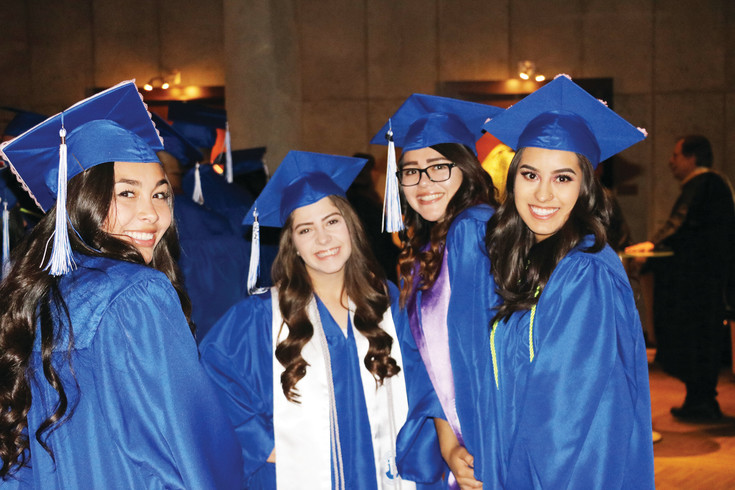 Four Alameda High School students gather while awaiting the beginning of their graduation ceremony on May 23 in downtown Denver.