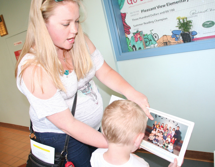 Rebecca Harris shows her 5-year-old son Jamison a picture of herself and former classmates in a yearbook that was set out for Pleasant View Elementary's closing ceremony on May 23.