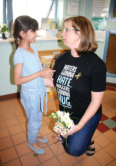 Jana Alqahtani, 8, says a goodbye to Pleasant View Elementary School Principal Janace Fischer on May 23 during the school's closing ceremony.