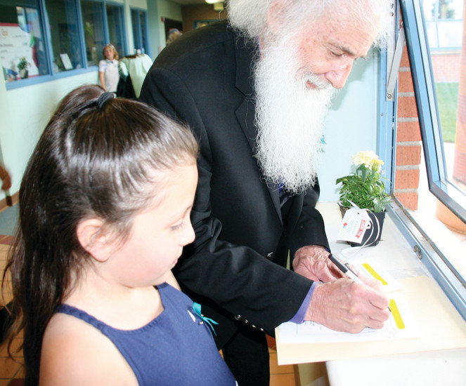 Harmonee Patterson, a second grader at Pleasant View Elementary School, watches Pleasant View alumni Dan Willard, 75, sign her program at the school's closing ceremony on May 23.