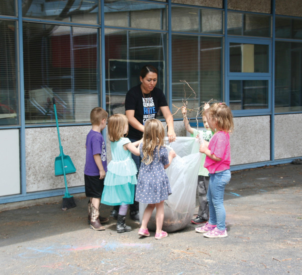 Pleasant View Elementary preschoolers help their teacher Erika Bylon clean up the courtyard on May 23 in preparation for the school's closing ceremony later that evening.