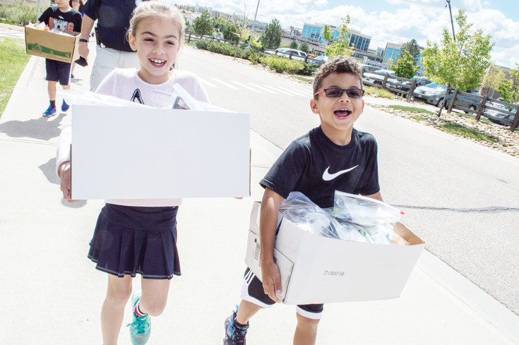 Angelika Korniyekl and Keno Woods carry boxes of their bags for the homeless from their classroom to a police car.