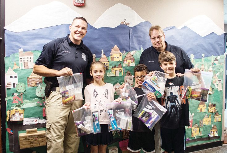 Kyle Maddox, Angelika Korniyekl, Keno Woods and Colton Holmes pose with the care packages they made to be give out to the homeless.