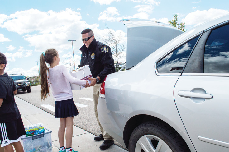 Angelika Korniyekl hands Officer Kyle Maddox a bag of care packages. Maddox will distribut the bags to Lone Tree police officers to be given to homeless people throughout the community.