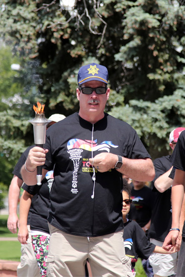 Douglas County Sheriff Tony Spurlock carries ones of three torches at the Law Enforcement Torch Run for Special Olympics Colorado.