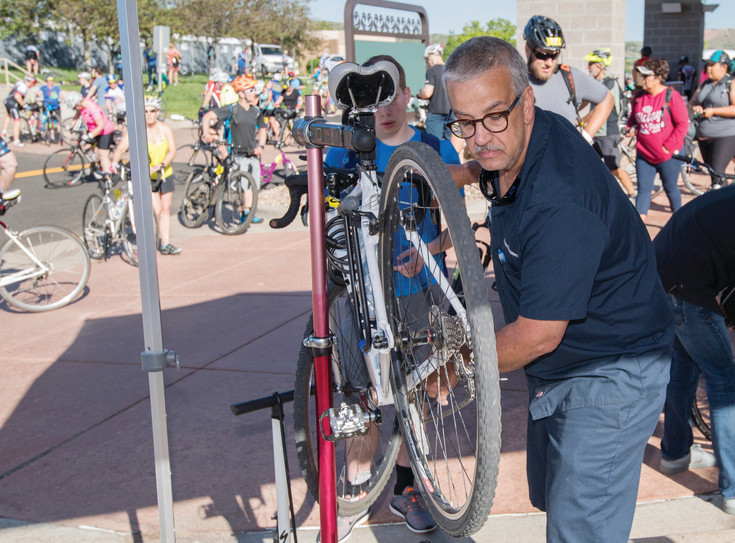 Highlands Ranch BikeSource employee Tony Valenti makes a quick repair on a riders shifter mechanism.  Mechanics from BikeSource were up before dawn helping hundreds of riders make some last minute adjustments before race-time.