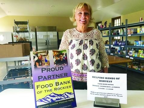 Volunteer Tammy Marshall stands by the signage at the Harvest Bible Church food bank and Helping Hands of Harvest food pantry in Elizabeth.