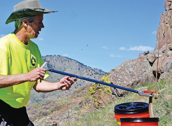 Bryon Shipley prepares to release a rattlesnake on the south face of North Table Mountain in Golden on Saturday, May 6. Shipley works for Adaptation Environmental Services, which is rounding up 20 snakes to microchip then release to track for research.