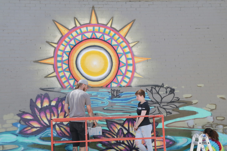 Team members work on the mural they are creating on one of the walls in Englewood's west paseo. Six Englewood High School students took part in the Museum of Arts design and build program focused on planning and creating public art.