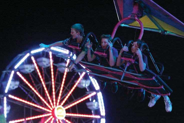 Connor McCarthy, 12, left, waves to the crowd below as Javen Shopp, 13, center, and Grayson Hardy, 12, hold on during the first night of the Parker Days festival. Rides roared and the weather held on June 8 to give attendees the opportunity for an early turn on the rides and attractions at the annual event.