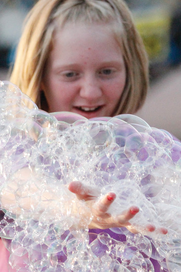 Amber Winkler, 11, gets more than a handful from a bubble machine spraying East Mainstreet with suds on the first evening of festivities at the Parker Days festival on June 8. Other events that evening included a concert by the 6 Million Dollar Band and headliner Bret Michaels of the '80s metal group Poison.