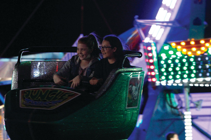 Ten-year-old Shannon France, left, and her friend Martina Merino, 10, enjoy a whirling trip on the Jungle Twist. The young Parker residents were among more than a thousand attendees for the Parker Days festival's first night on June 8.