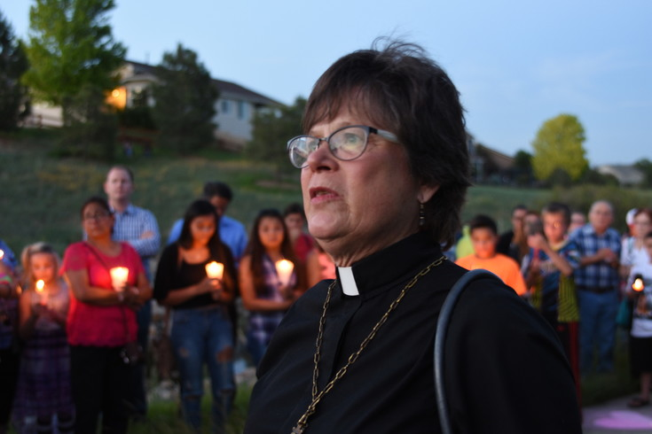 "Reverend Kari Reiquam, Pastor of St. John's Lutheran Church, 11040 Colorado Boulevard, Thornton, speaks to assembled attendees of last Saturday's candlelight vigil for the late Kiaya Campbell, whose body was found near this spot last Thursday. "" It's easy to feel fear, when evil occurs so close to us, ""said Rev. Reiquam. ""But we must trust in the faith of the community. For love heals the sorrow and the pain, and the fear. So I'm glad that for tonight, that we've come out of our houses and out of isolation. Let us meet each other and come to know our neighbors and build trust. For goodness does come, there is grace. There is a love that conquers hate""."