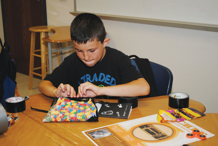 "Keagan, who will be a fifth-grader next year, works on a duct tape purse during the Duct Tape Billionaire module. He is making it to help his parents ""be more organized."""