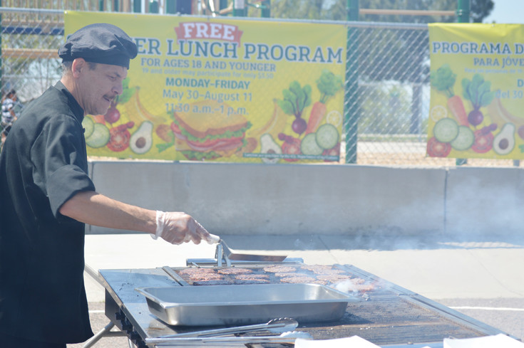 David Trujillo, kitchen manager for catering contractor Chartwells, flips burgers Wednesday June 7 at Westminster's Hodgkins Elementary School, 3465 W. 67th Ave., for the statewide kick-off to the summer meal program. Chartwells is the contractor hired by Westminster Public Schools to prepare school lunches throughout the year.