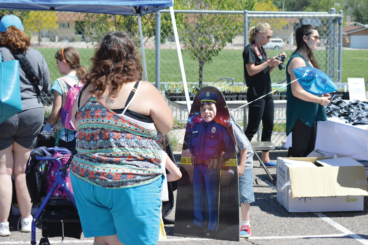 Michael Hendricks, 7, smiles for the camera behind a police officer cutout while Grandmother Becca Emme takes  a picture. The two turned up June 7 at Hodgkins Elementary School for the kick-off of the summer lunch program both in Westminster and across the state.