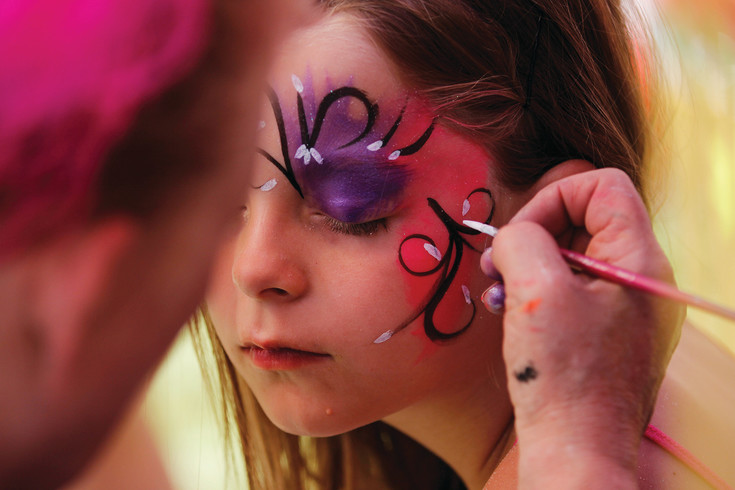 Grace Thomas, 6, closes her eyes as the finishing touches are applied to her face paint. Thomas, a Parker resident, came to the festival with her aunt, Jessica Taylor.