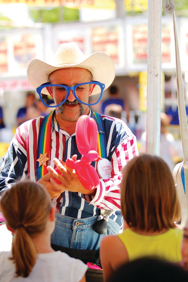 """Uncle Ed"" takes a break from his regular gig with the Salida Circus to twist balloon animals for young patrons at the Parker Days festival on June 10. Ed says he enjoys working Parker Days because ""the people are friendly."""