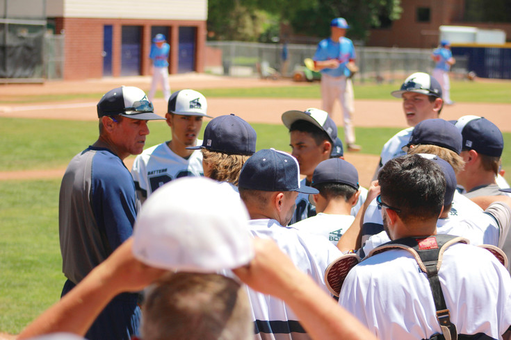 Batter's Box coach Lee Martin talks to his team between innings of a game during the Cherry Creek Classic baseball tournament.