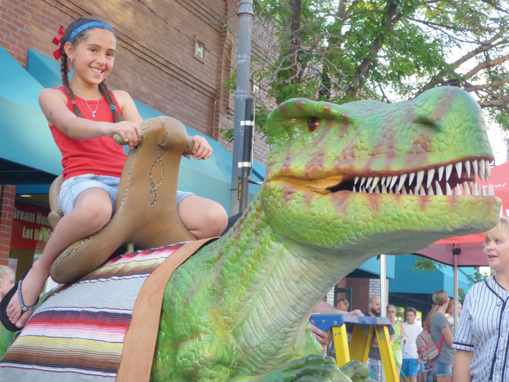 Izabella Creekmore, 10, takes a ride on an animatronic T. Rex.