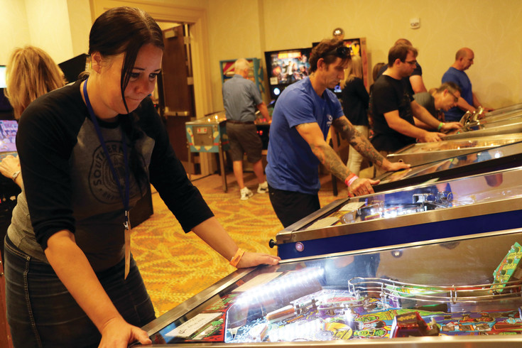 Helena Higgins, 42, left, plays a pinball machine at the Pinball Showdown and Gameroom Expo on June 9 at Denver Marriott South, 10345 Park Meadows Drive. In Dallas last month, Higgins won the women's pinball world championship.