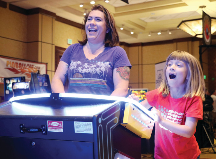 Cheyanne Witty and her 6-year-old daughter, Arith, play a game of lifesize Pac-Man at the 14th annual Pinball Showdown and Gameroom Expo at Denver Marriott South at Park Meadows, 10345 Park Meadows Drive, Lone Tree.