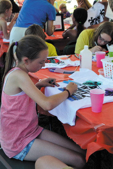 Macey Tallick, 11, from Lakewood, colors in her memorable Sand in the City T-shirt preparing to have it tie dyed as part of last year's kid-friendly extra events.
