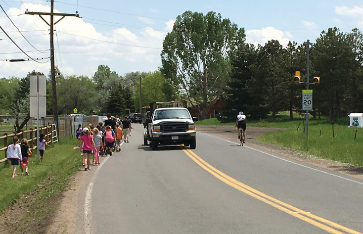A large group of students and a bicyclist share West 50th Avenue with traffic shortly before the school year ended. In May, the Colorado Department of Transportation provided a Safe Routes to School grant to Jefferson County to help fund a sidewalk project along West 50th Avenue.
