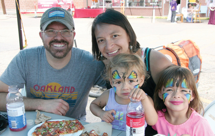 The Prevo family — Tony, Patty, two-year-old Nyan and four-year-old Elliana — enjoy some food at the Ridge at 38 Criterium June 11. They planned on riding the race course during the family ride at noon. 