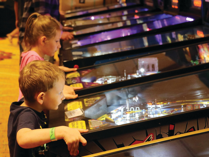 Link Sampsel, 4, front, and his sister, Milla, 6, play vintage pinball machines at the Pinball Showdown and Gameroom Expo. Their father brings his game machines to the annual event  for other people to try.