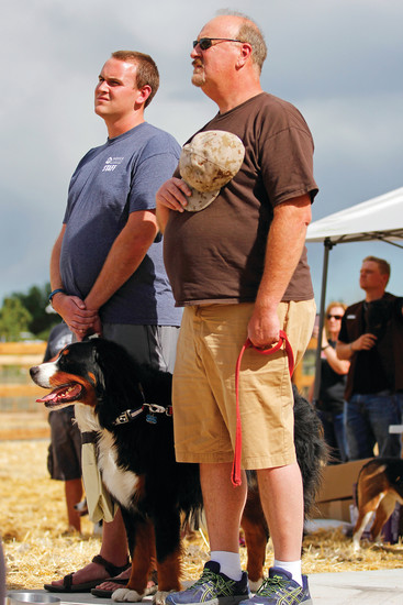 Parker resident Geoff Harger, his father, Tom and their dog, Hoss, look on during Alicia Pope's rendition of The National Anthem during the dedication ceremony for the USMC Cpl. David M. Sonka Dog Park. Approximately 200 people came to the dedication to honor Cpl. Sonka, a graduate of Chaparral High School who was killed ialong with his service dog, Flex, in Afghnistan in 2013.