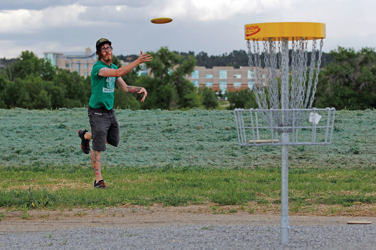 Joe Galkin takes a few practice putts at the Westcreek Disc Golf Course on its opening day, June 14. Galkin skipped his normal Wednesday disc golf group in Greenwood Village to try the course, and said he was impressed by the abundant trees and open space.