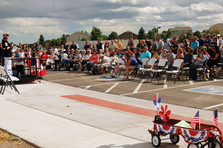 Attendees listen to a speech by USMC Master Gunnery Sgt. John Alen during a ceremony honoring Cpl. David M. Sonka and officially dedicating Parker's first dog park in Sonka's name. Sonka and his Multi-Purpose Canine Flex were killed in Afghanistan in 2013.