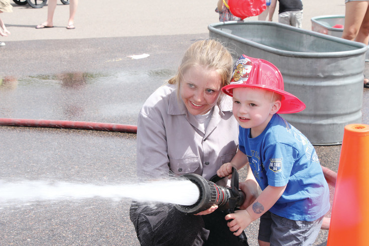 Volunteer Briana Scherrer, left, helps 3-year-old Liam Uselton direct the spray of the hose during the 2015 Fire Muster activities in the parking lot of Arapahoe Community College. The celebration returns to Littleton on June 15.