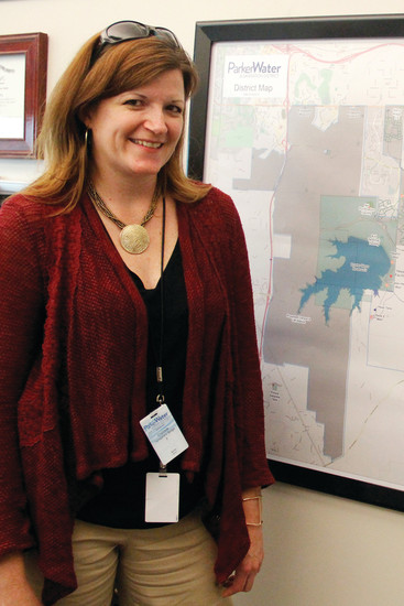 Rebecca Tejada, senior project manager for the Parker Water and Sanitation District, stands next to a map of the district's boundaries and water sources. Tejada says part of her job is constantly searching for new sources of renewable water to ensure a stable supply for the future.