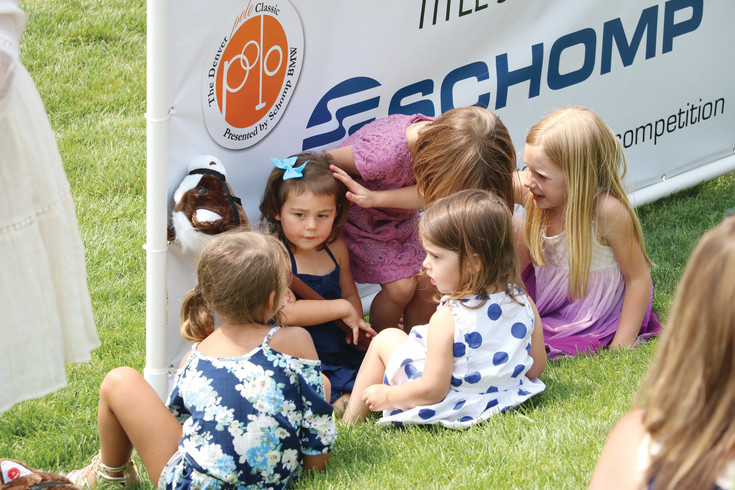 A group of young girls takes shade behind a sign at the Denver Polo Classic Family Day on June 24 at Polo Reserve, 4400 W. Mineral Ave., Littleton.