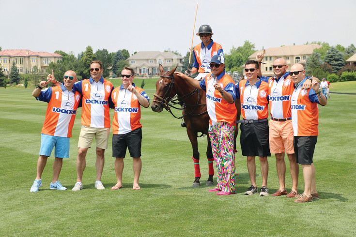 Repping their Lockton gear, a group of men surround a polo player at the June 24 Denver Polo Classic Family Day at Polo Reserve, 4400 W. Mineral Ave., Littleton. Lockton Championship Day, when the Denver Polo Classic champion is crowned, commenced the following day.