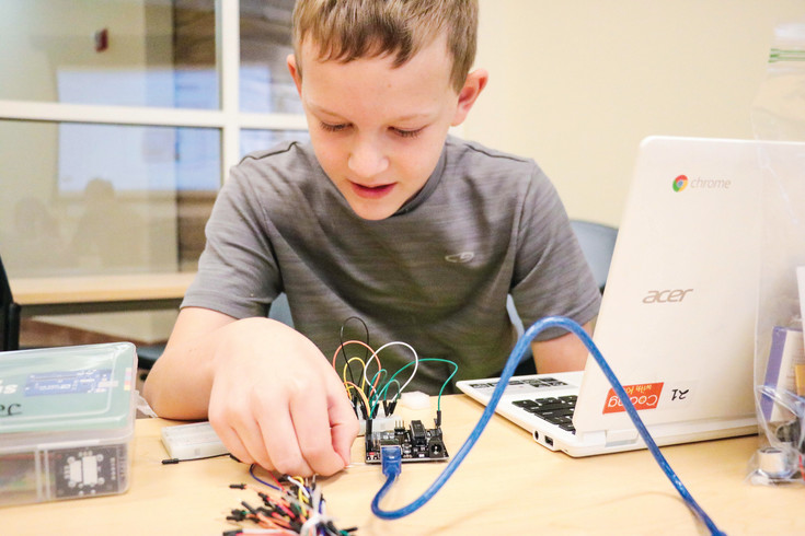 Jack Hopkins, 10, messes with the wires on his circuit board to complete the assignment during a University of Colorado South Denver Coding with Kids camp on June 23.