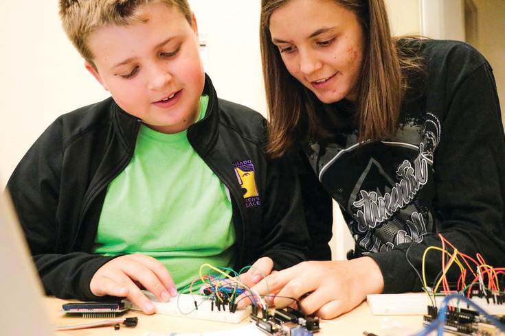 Owen Wolfinger, 12, and Jessie Mickus, 15, work on a circuit board and attempt to get a message to go across a screen during a University of Colorado South Denver Coding with Kids camp.