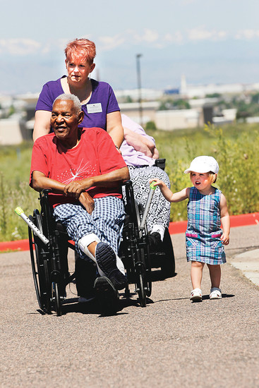 Kristin Kreitner, a physical therapy assistant at Avantara Crown point, pushes client Louis McRae with a little help from her granddaughter, Marilyn, 2. About 30 clients from Avantara and Chelsea Place Memory Care in Aurora took laps around Avantara's parking lot to raise money for the American Alzheimer's Association.
