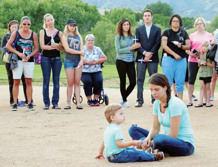 Olivia Beare and her 20-month-old son, Brian, sit in the center of a prayer circle at a June 29 vigil for her husband, Steven Beare, a Littleton police officer who two weeks ago went missing while hiking in Russia. The gathering was held at Roxborough Park, 7673 N. Rampart Range Road.