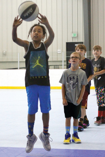 "Denver resident Ben Lee, 8, practices free throws at the Chauncey Billups Basketball Academy. Lee says his nickname on the court in his school in ""Anklebreaker."""