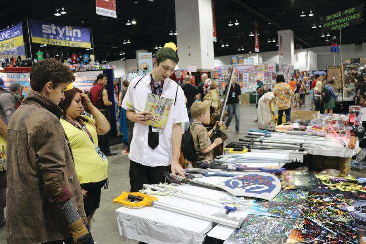 Visitors to Denver Comic Con check out replica weapons from favorite series, like The Legend of Zelda, at the Colorado Convention Center on June 30.