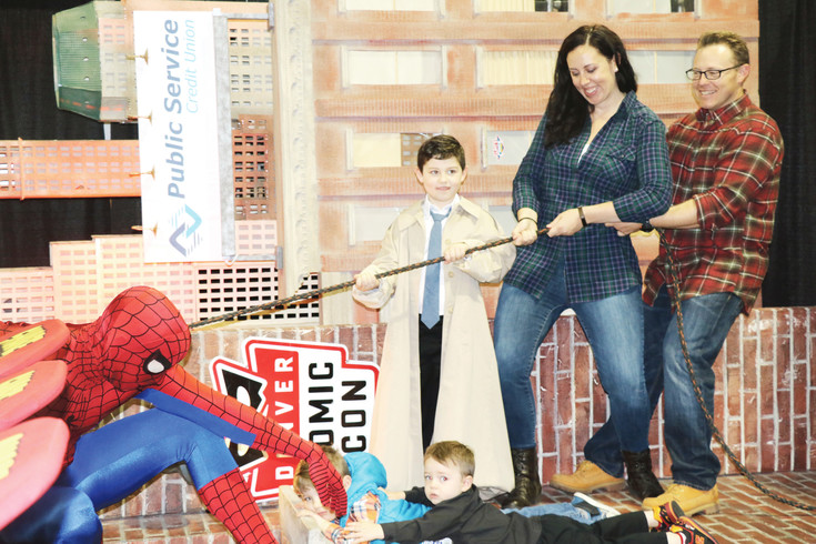 The Burns Family, from Aurora, poses for a wall-climbing photo with Spider Man at Denver Comic Con on July 1.