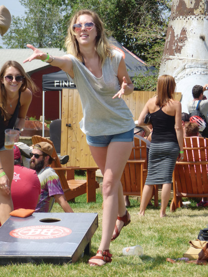 "Sarah McKay tosses a beanbag in a game of cornhole. ""I leave the scorekeeping up to the other guys,"" she said."