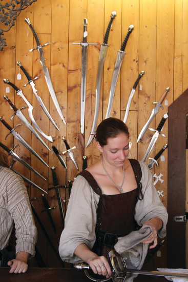 Kat Archer cleans merchandise at the Legacy Forge, which sells knives and swords at the Colorado Renaissance Festival. Archer has worked with the festival for nine years.