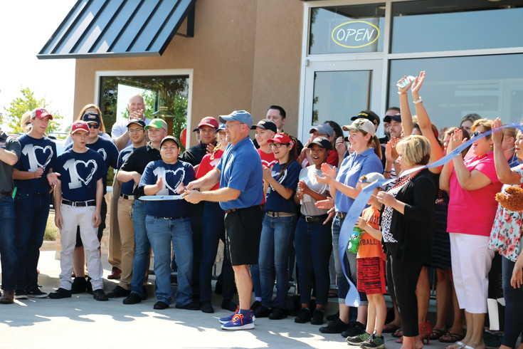 General manager David Cannon cuts a blue ribbon at the grand opening of Raising Cane's, a Louisiana-based restaurant known for its chicken fingers that opened July 6 at 1108 Corporal Max Donahue Lane, across from Town Center North.