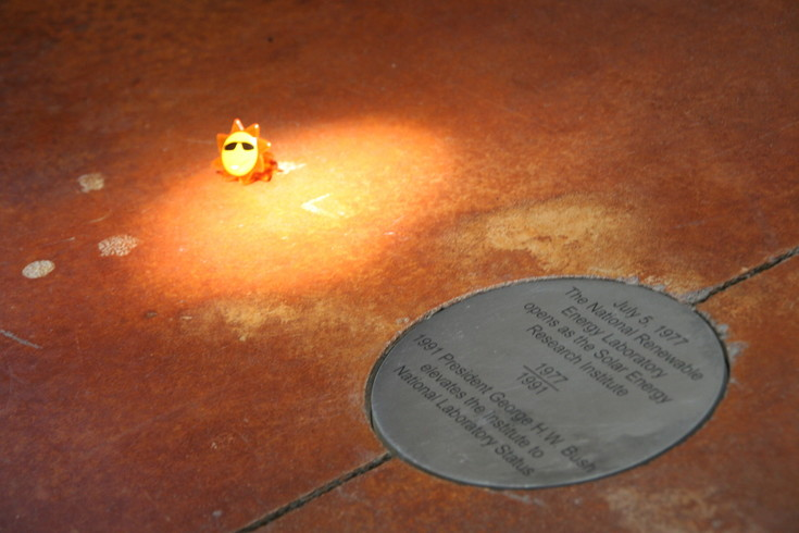 The sun makes its way through a skylight in the ceiling to light up a commemorative medallion on the floor to officially mark the 40th anniversary of the National Renewable Energy Laboratory (NREL) on July 5.