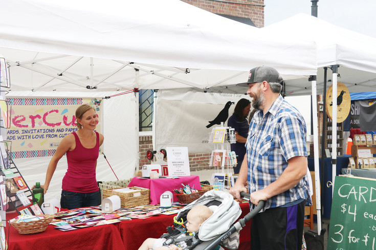 Chelsea Dunn, owner of Paper Cuts Greeting Cards, visits with customers at the first Edgewater Market and Music event on June 29. The market features about 34 vendors of all kinds displaying their wares Thursdays through Sept. 7.