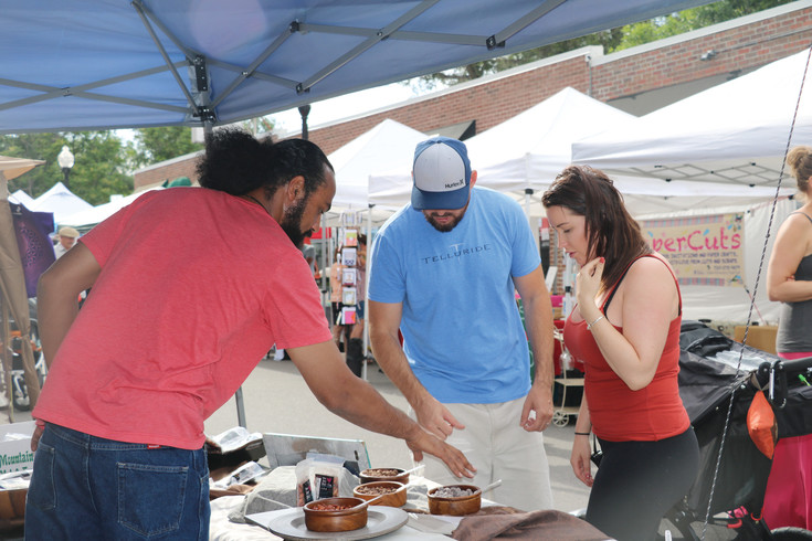 Melvin Woolley with the Joy Nut Company, offers samples to shoppers at the first Edgewater Market and Music event on June 29. The market runs at West 25th Avenue and Sheridan Boulevard on Thursdays through Sept. 7.